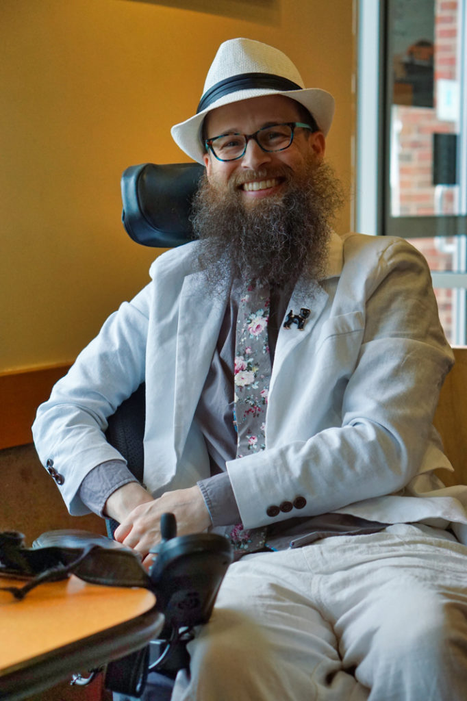 The illustrious photographer, Brad!  He is a bearded man wearing white linen pants and blazer, a grey shirt, a grey tie with white and pink roses, a white hat, and a black dog pin on his lapel.  He is smiling broadly.
