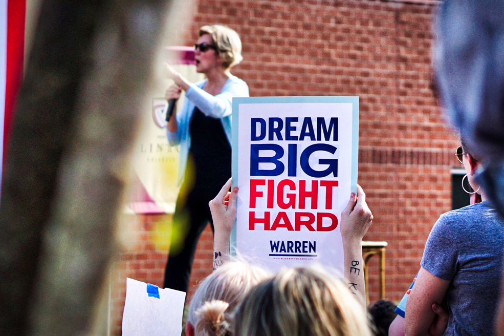 "Elizabeth Warren gestures in the background.  In the foreground someone holds up a sign that reads ""Dream big, fight hard""."