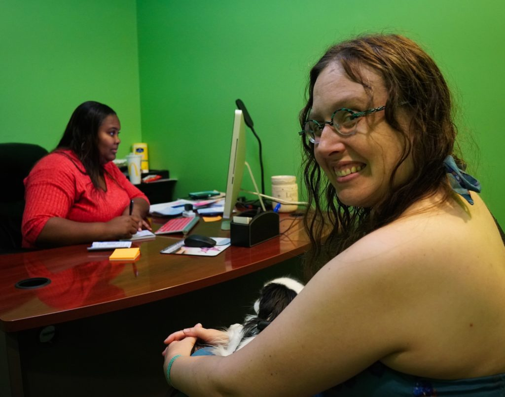 Veronica smiles over her shoulder during an appointment with her nurse practitioner.  Hestia lies on Veronica's lap.