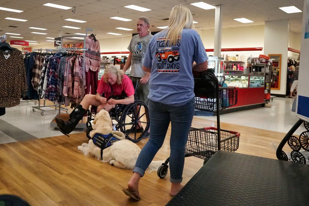 Inside TJ Maxx Barbara treats Tripper as he lies down ignoring a woman passing him with a shopping cart.