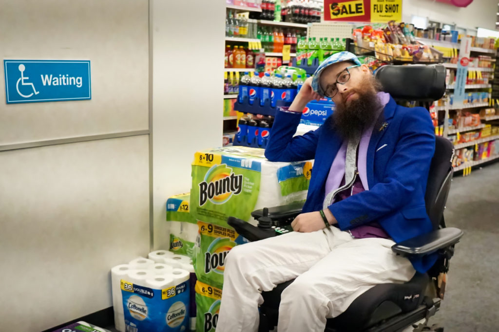 """On the wall a sign has the universal accessibility symbol (person in wheelchair) and says """"waiting"""".  In the wheelchair waiting area there is a pile of paper towels.  Brad rests one arm on the pile of paper towels and looks at the camera in a resigned way."""