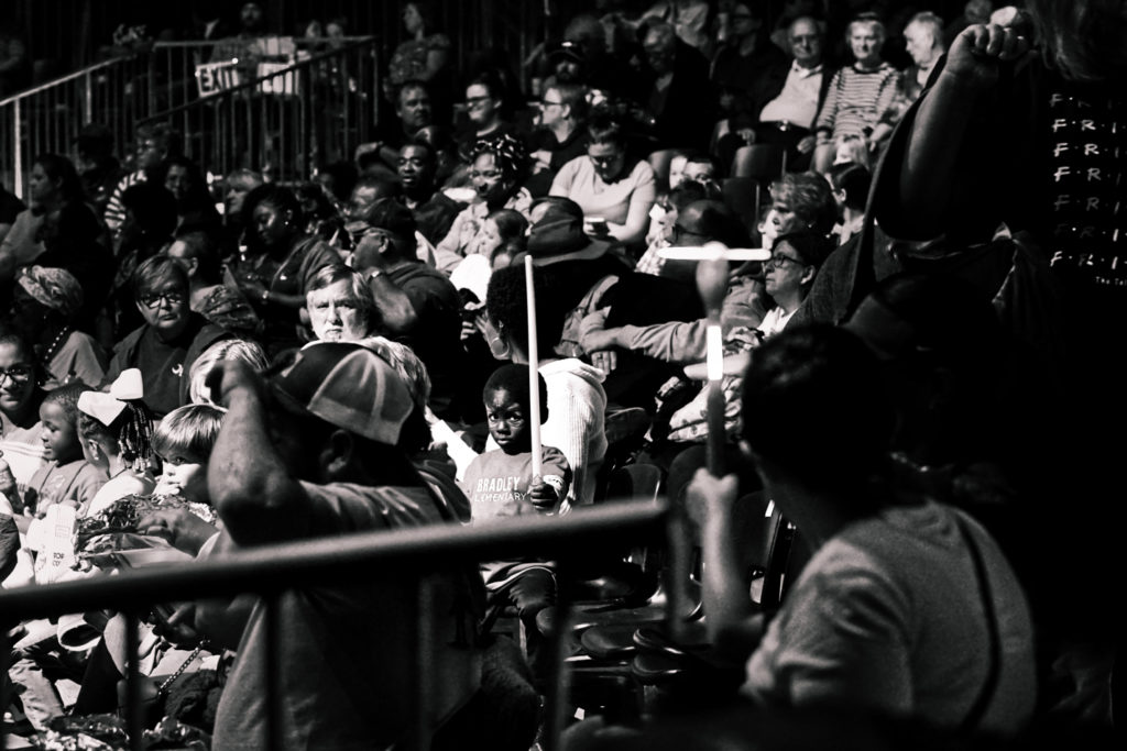 Black and white shot of the crowd at the circus.  At the center of the picture is a young boy with his face painted swinging a light-up sword.