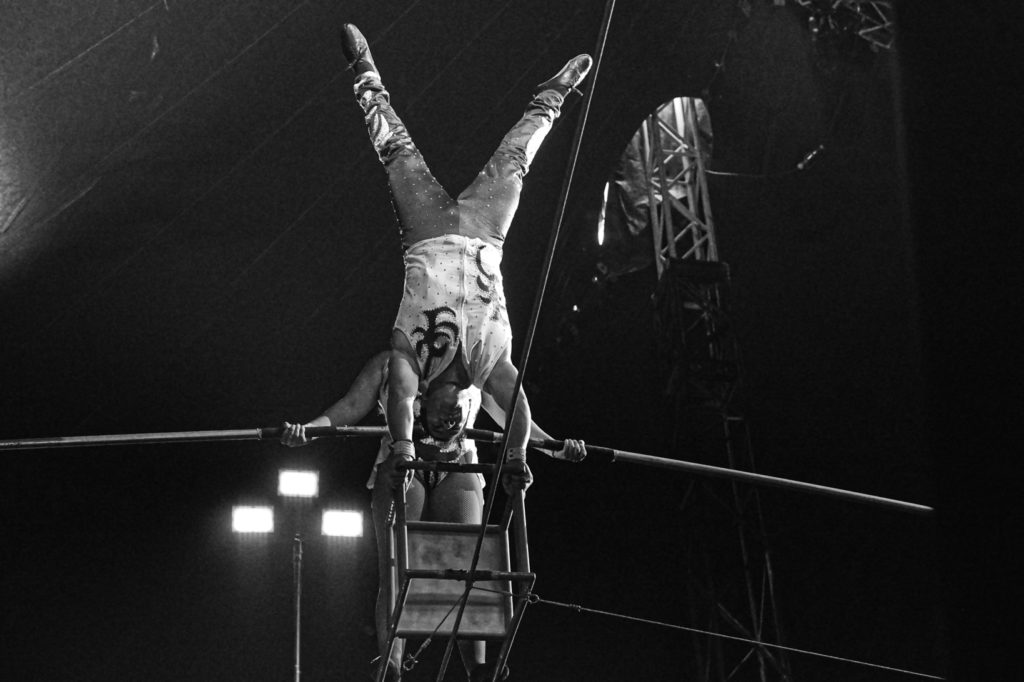 A woman stands on a chair balanced on a tightrope.  A man does a handstand on the other end of the chair.