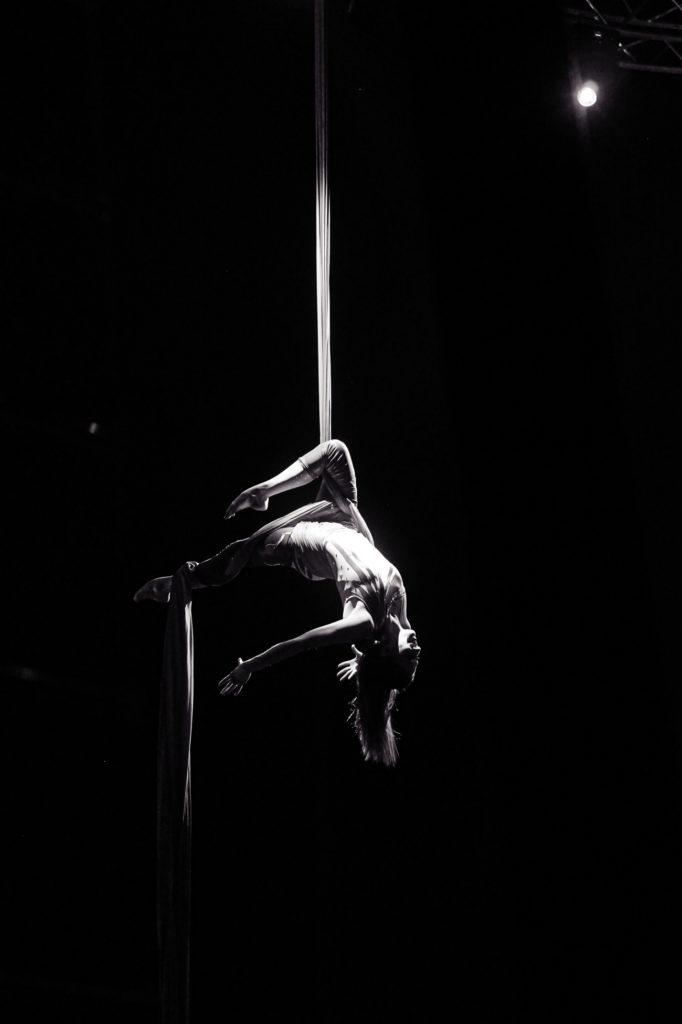 An acrobat hanging from a fabric line doing a dramatic pose in black and white.