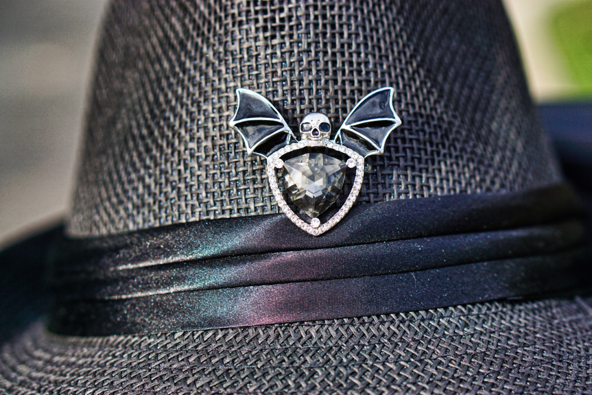 This is a closeup of the pin in Brad's black fedora.  It has a large triangular black gem surrounded by rhinestones.  There are black bat wings coming out of the top of the stone, and a skull on top of the stone in between the wings.