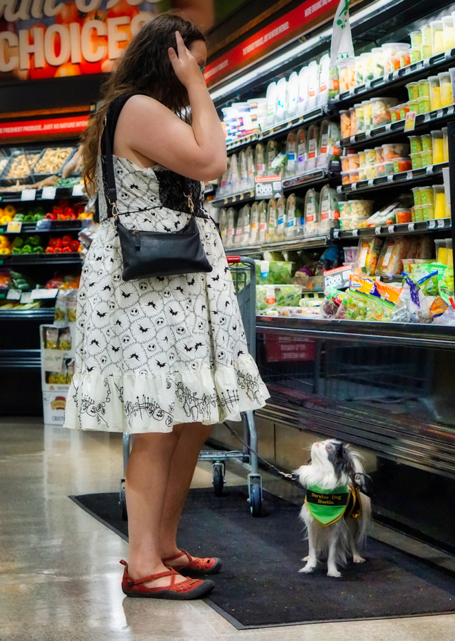 In this candid shot, Veronica looks at grapes in the store, while Hestia stands in front of her looking up at Veronica's face.