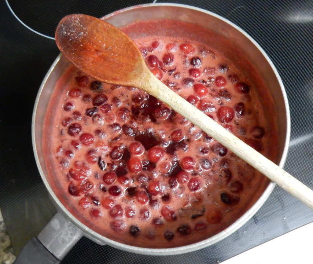 An aluminum pot filled with red liquid with burst cranberries.  This batch is the agave nectar batch, so it is smaller and the liquid has a more reddish appearance.