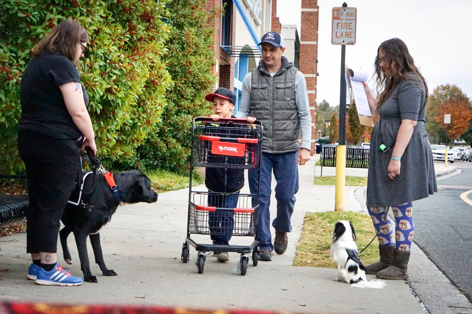 A family pushing a shopping cart passes Kristi with Jax and Veronica with Hestia.