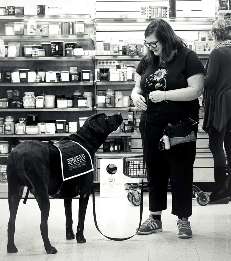 A black and white photo of Kristi and Jax looking into each others' eyes while standing in the store.