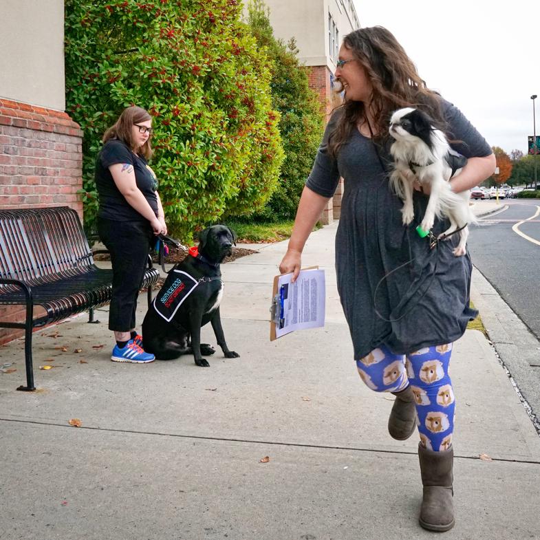 Veronica carrying Hestia runs past Kristi with Jax.