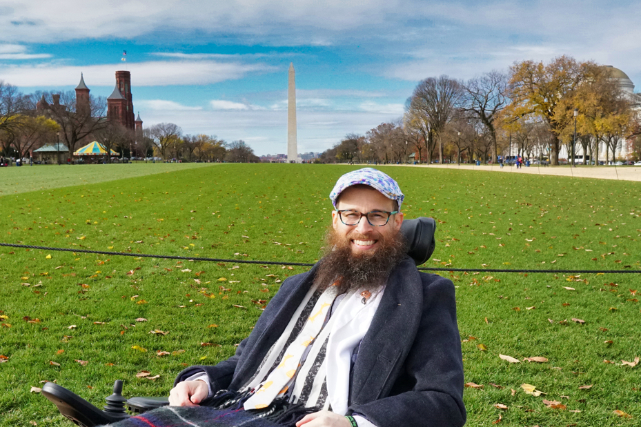 Brad is wearing a grey coat, a white blazer, a fox tie, a fox pin, and a blue and purple flower hat with lace on it.  He poses in front of the Washington Monument far in the background.