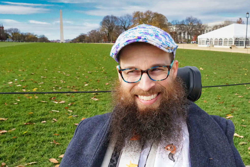 Brad smiles and looks to his right with the Washington Monument in the background.