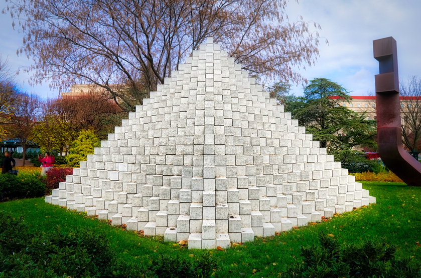 A sculpture of concrete blocks arranged in a pyramid shape.  It is very striking, especially the white blocks against the green grass and the blue sky.