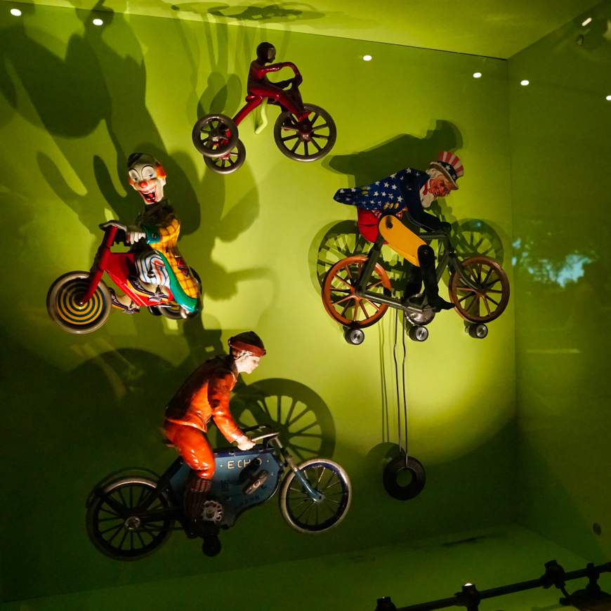 In front of a green background, several old bicyclist toys are displayed on a wall. One is a creepy clown, smiling while looking your way.