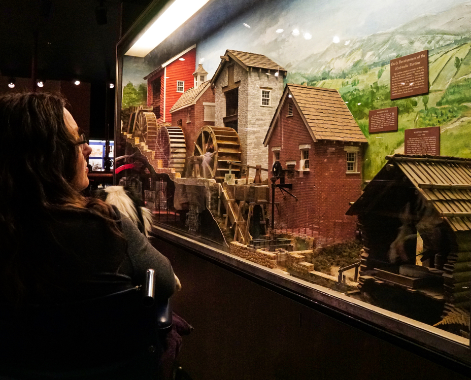 Veronica looks at a diorama of model waterwheels along a village.