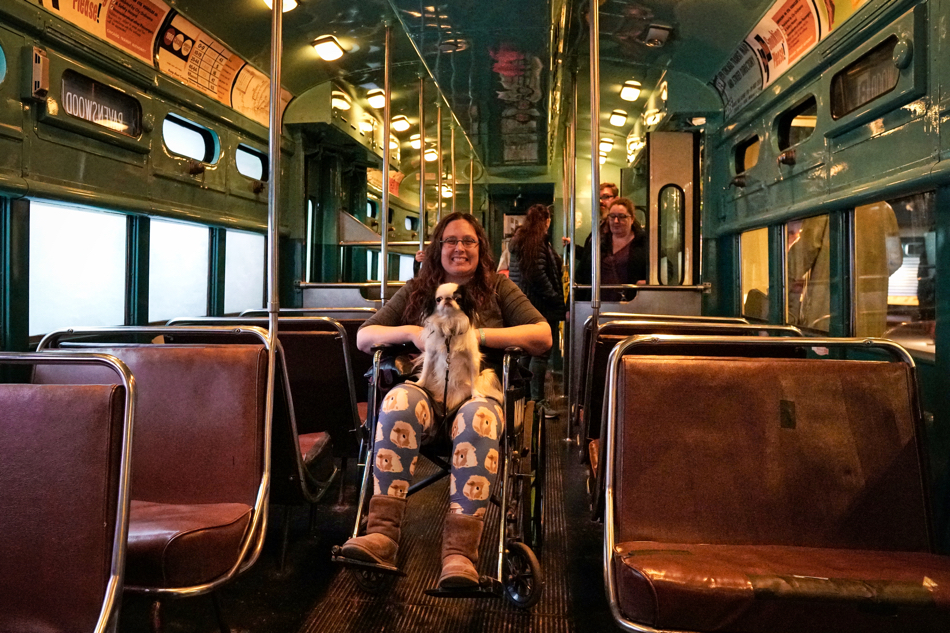 Veronica in a wheelchair in the aisle of a subway train in the museum.  Hestia sits on her lap and they both smile at the camera.