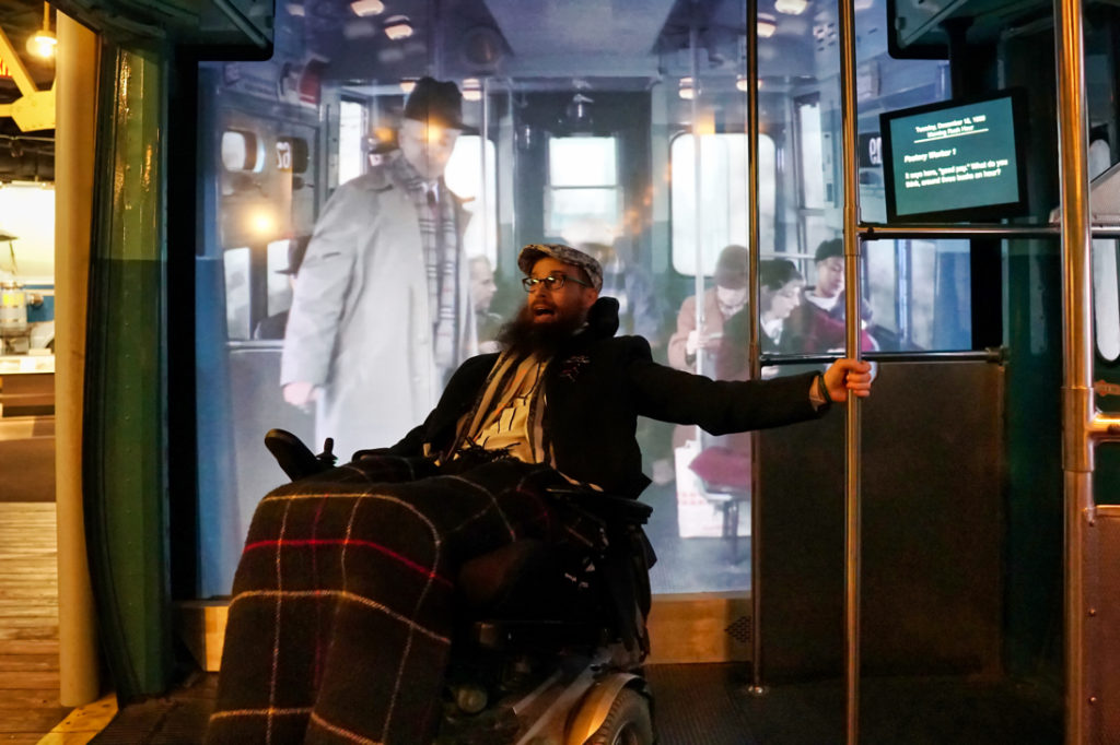 Brad holds onto a pole in the subway train as if he's sliding around, and in the background a movie is playing of what life on the subway would have been like in the 70s.
