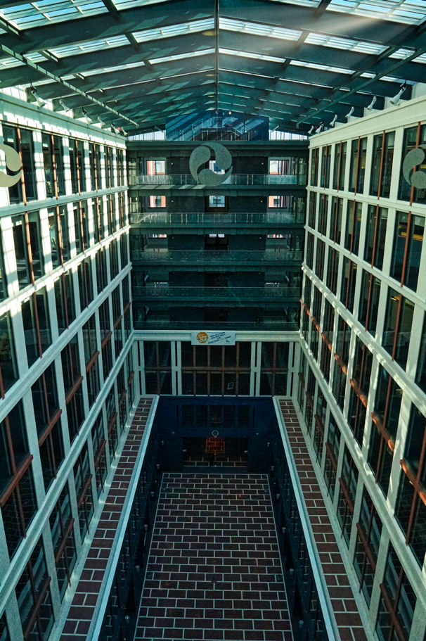 The interior atrium of DOT is a tall space with a brick floor and lots of windows and open light.
