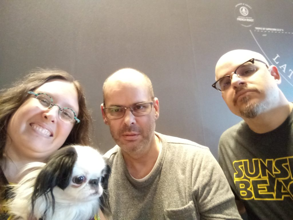 A selfie of us three!  I am a woman with long brown curly hair on the left.  On my lap is a black and white dog with a smushed nose.  In the middle is Dan, who has on a grey shirt, has a bit of a beard, and is wearing glasses.  Doc is on the right, wearing a Sunset Beach shirt, with a goatee and glasses.  I am the only one smiling, everyone else is looking serious!