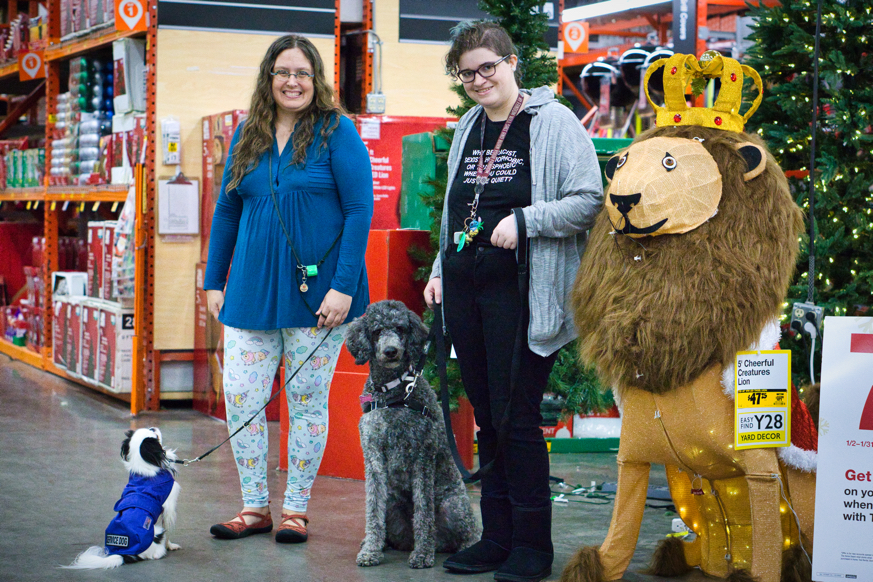 Veronica, Hestia, Scarlet, and Mia stand next to a giant lion wearing a crown in Home Depot.  Everyone except Hestia is looking at the camera.  Hestia is sitting in front of Veronica, looking up at her.