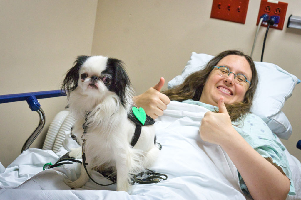 Veronica gives two thumbs up about her upcoming surgery as Hestia looks into the camera.