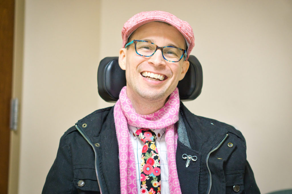 Brad is appropriately decked out for the situation with a pink hat and scarf, pink flower tie, black jacket, and a pin with the female reproductive system on it.
