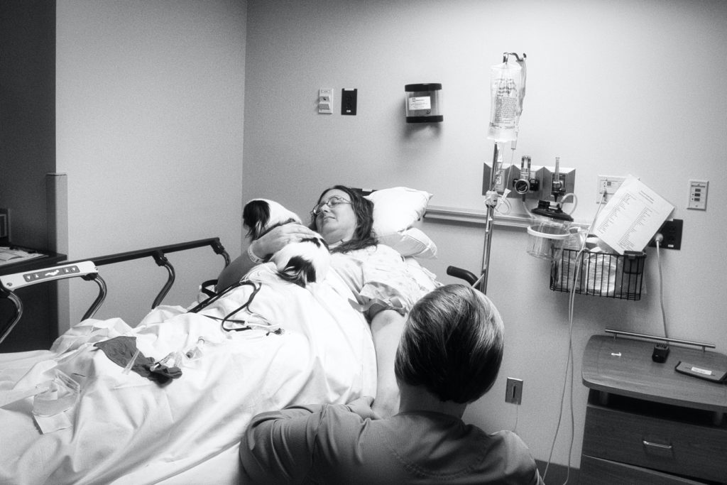A black and white picture of the nurse putting the IV in.  Veronica and Hestia look away.