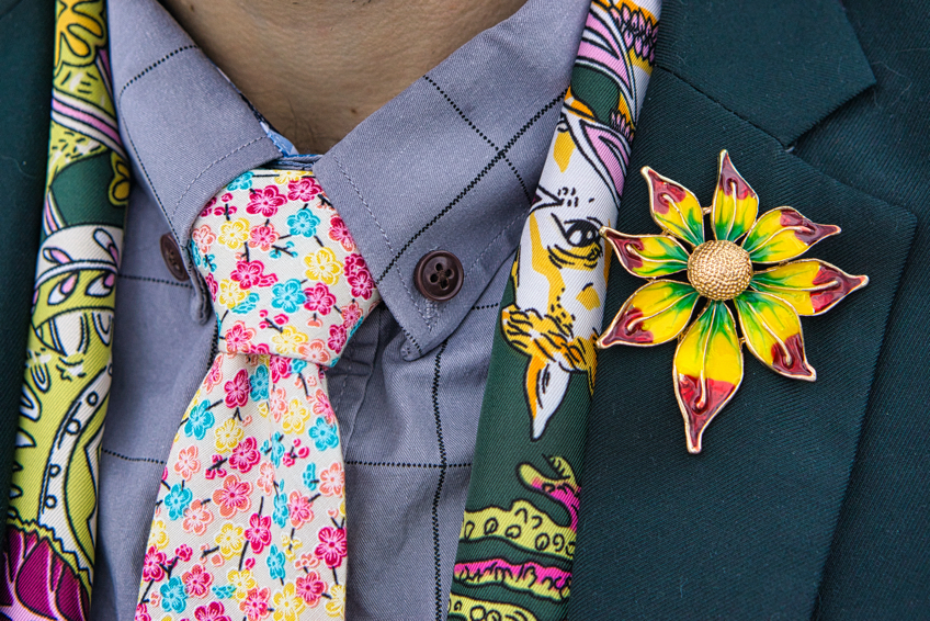 A closeup of Brad's large flower pin that is green and yellow and purple on the lapel of his green jacket.  He has a grey shirt on, and a tie with turquoise, pink, and yellow small flowers.  His scarf is green and purple and yellow and pink.