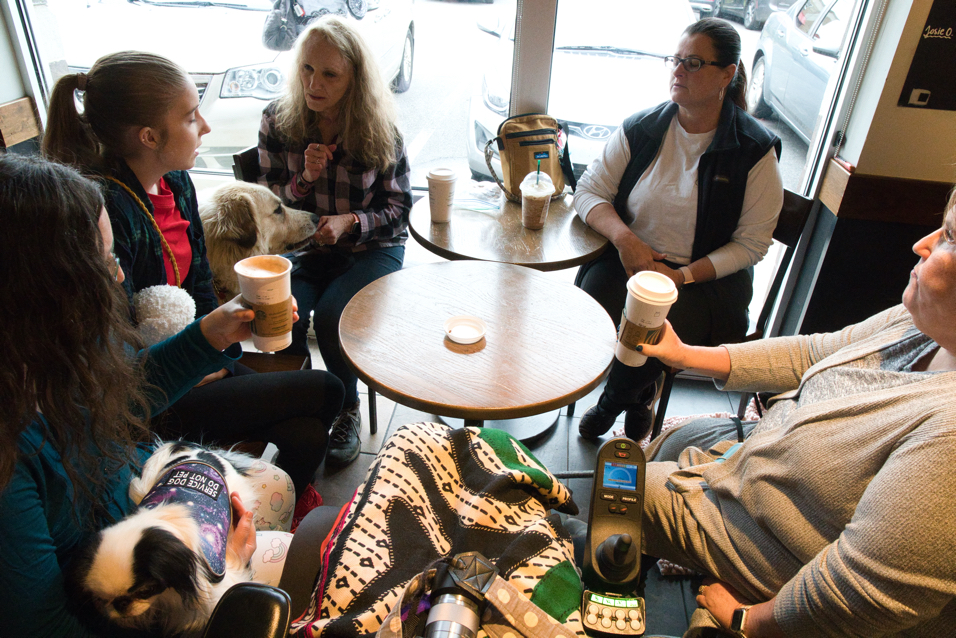 Everyone sits around the tables in Starbucks.