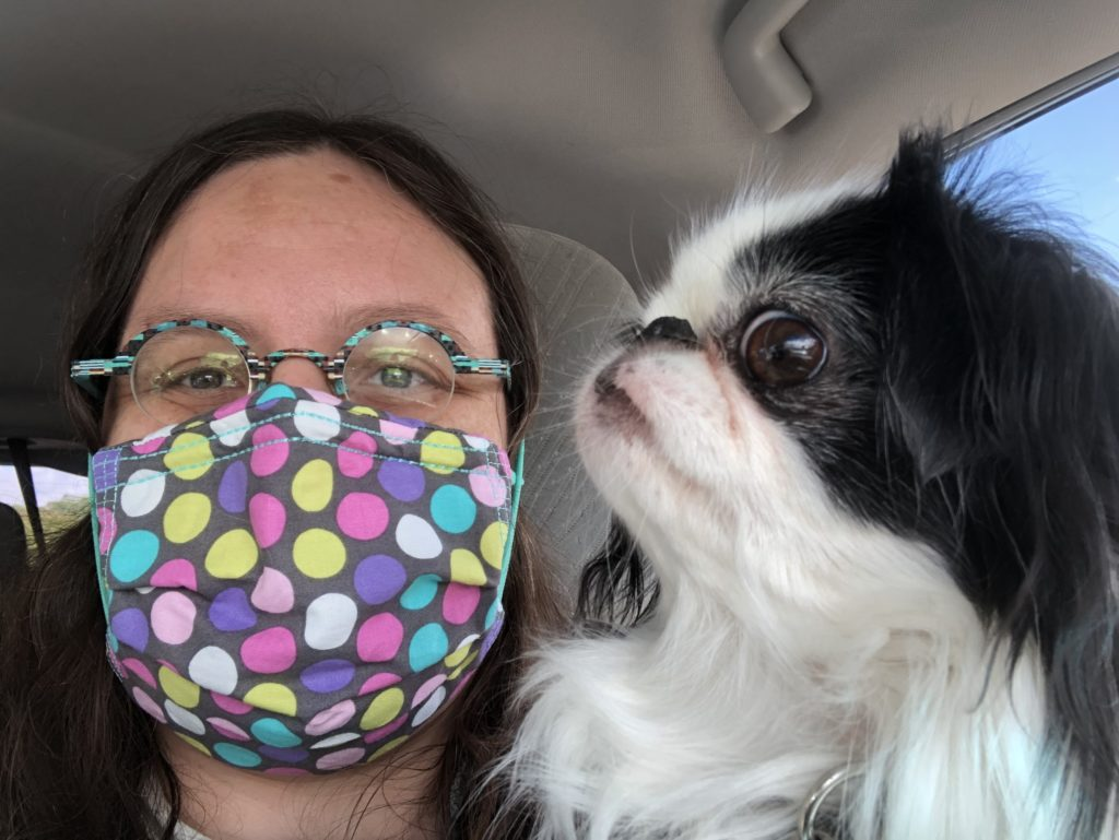 Veronica wearing a mask in the car with Hestia.