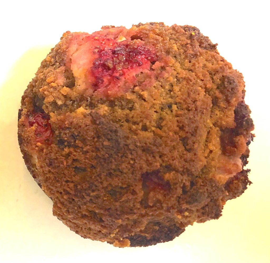 Brown muffins with red strawberries bursting out of the top.