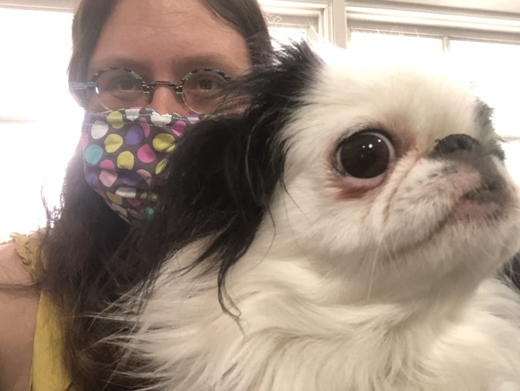 Veronica wearing a mask with multicolored polka dots on it with Hestia's face in the foreground.  This picture was taken in the waiting room.