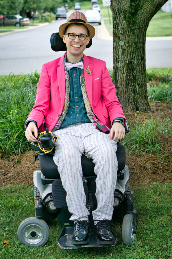 Brad in his powerchair smiling while posing in front of a tree.