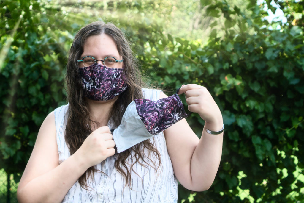 Veronica models a mask with a black background with a  marbled pink and white pattern on it.  She holds in her hands a matching mask that is half the same material and half grey.