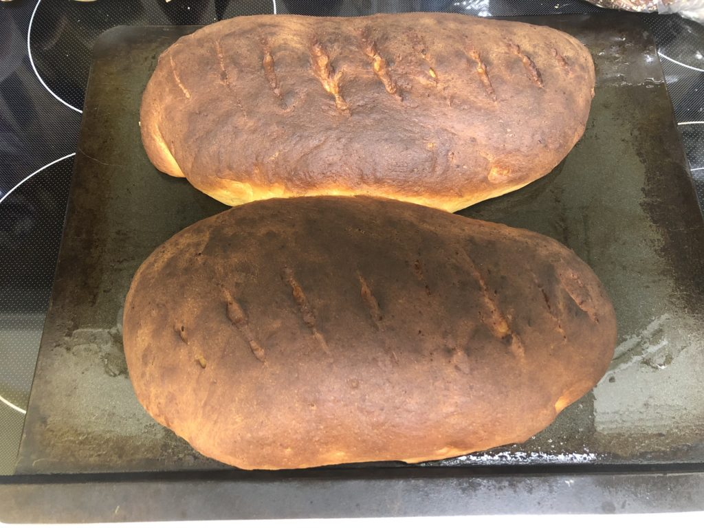 Two dark brown oblong loaves of bread on a black cookie sheet.