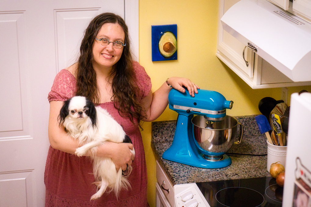 Shot from high above, a smiling white woman holds a small white and black dog and rests her hand on a dark teal mixer on a kitchen counter. A small painting of half an avocado hangs on a yellow wall behind her, with a white door and white cabinets on the perimeter.