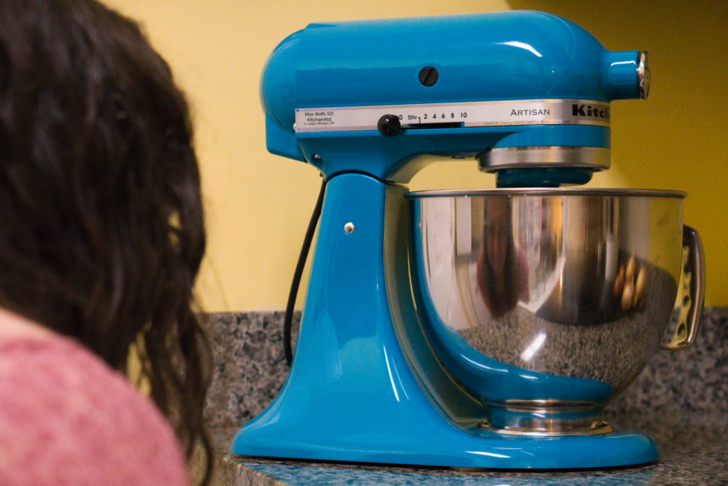Closeup of a dark teal Kitchenaid mixer on a gray granite countertop in front of a yellow wall. Blurry in the foreground on the left quarter of the picture is the back of a woman's head. Her smiling reflection is in the stainless steel bowl of the mixer.