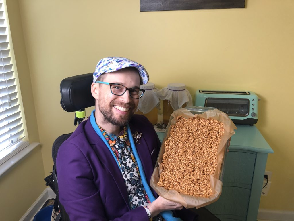 Brad is a man with a very very short beard wearing a multicolored flower shirt, a black and white flower tie, a blue scarf, a purple blazer, and a white hat with blue and purple flowers on it.  He holds up a 9x13 baking dish with rice krispie treats in it and smiles.