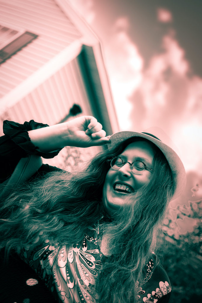 In this sepia tinted photo, Veronica hold the hat brim and laughs.