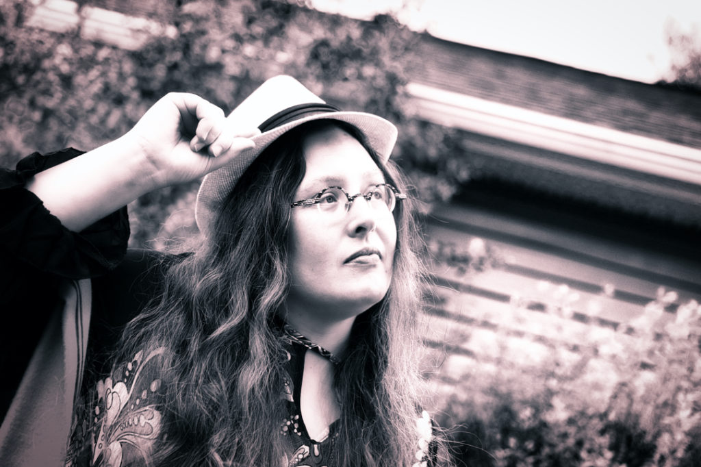 Another sepia photo of Veronica holding the hat brim, but she is serious in this one.